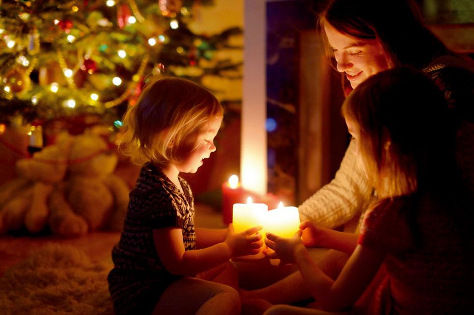 Kinder mit Mutter vor Weihnachtsbaum