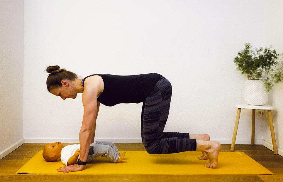 Mama mit Baby beim Sport auf einer Matte am Boden