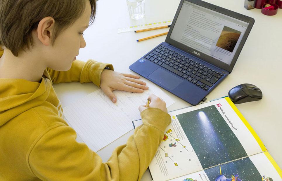 Junge mit Laptop am Schreibtisch beim Lernen