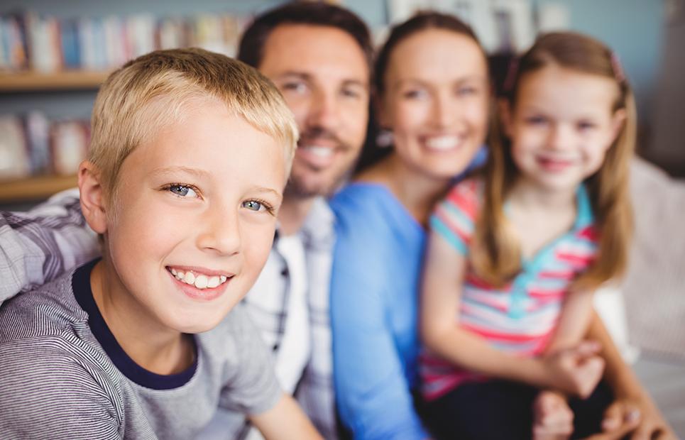 Familie mit zwei Kindern sitzen auf dem Sofa