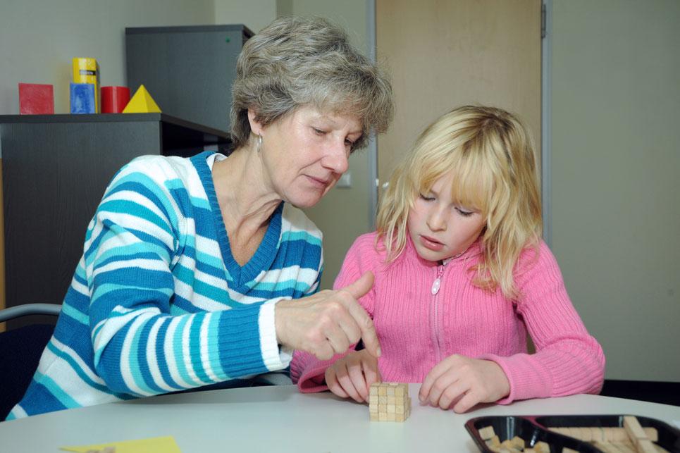 Frau erklärt einem Mädchen am Tisch eine Würfel-Aufgabe