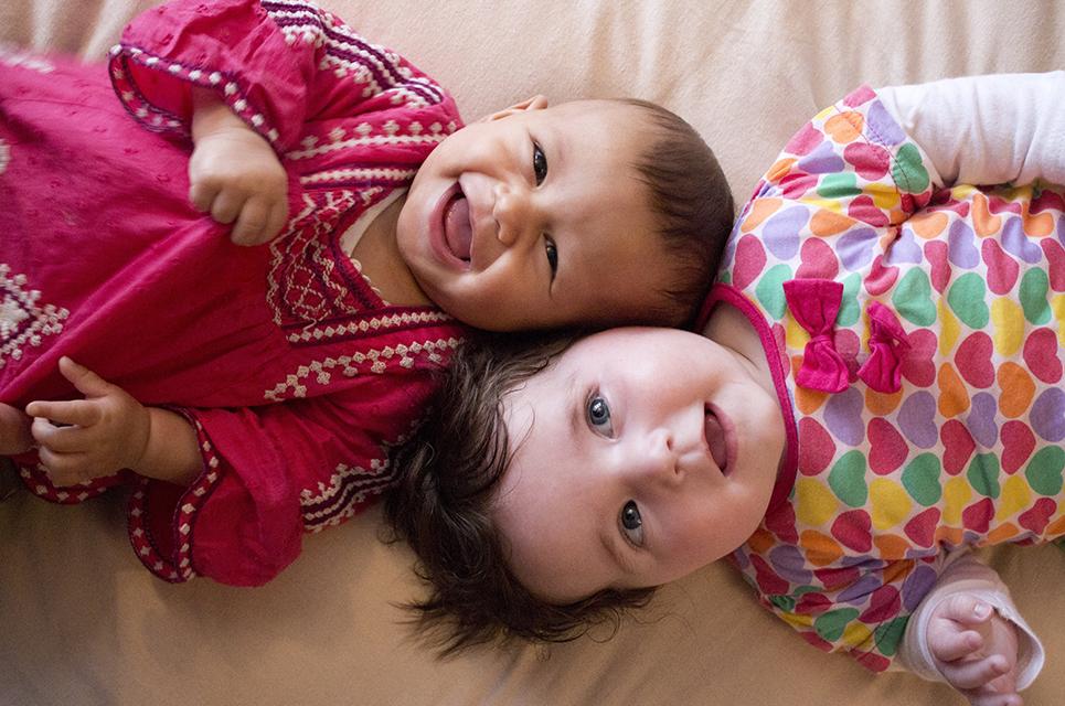 Ein Baby und ein Kleinkind liegen auf dem Rücken und schauen neugierig in die Kamera