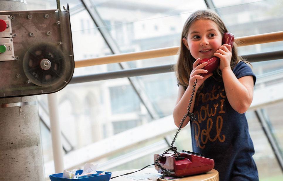 Mädchen mit Telefonhörer eines alten Telefonapparates am Ohr