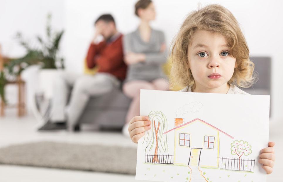 Kind hält traurig ein gemaltes Haus in der Hand, im Hintergrund sind die zerstrittenen Eltern zu sehen
