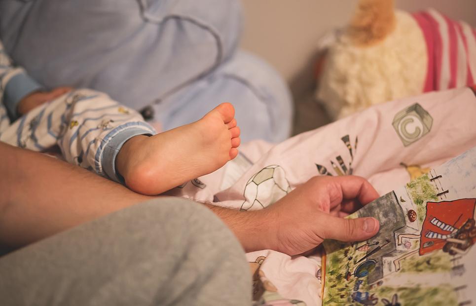 Vater liest eine Gute-Nacht-Geschichte vor.