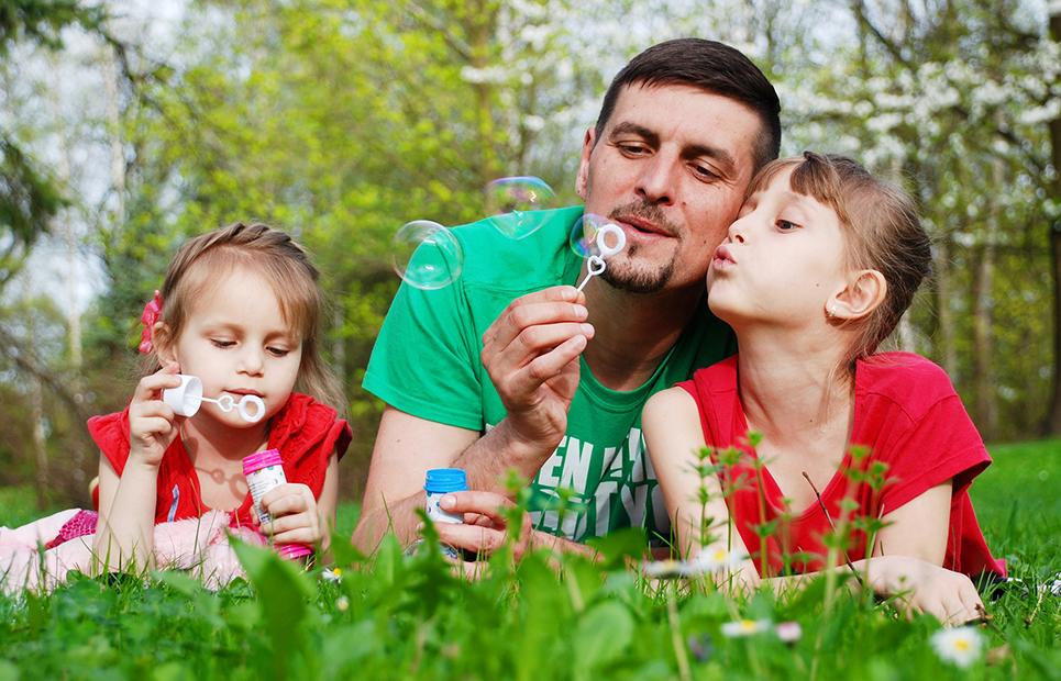 Vater und Töchter machen Seigenblasen