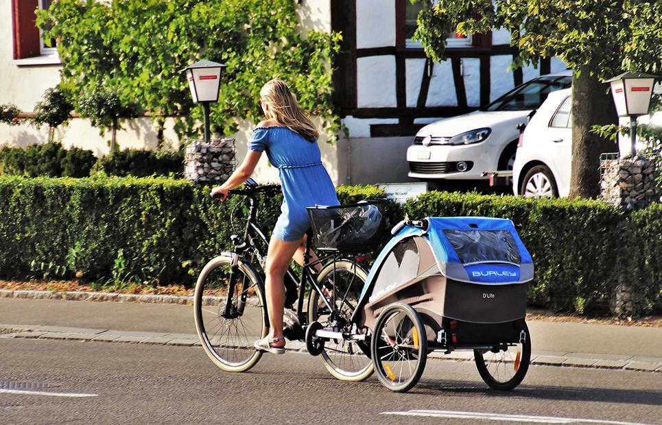 Frau fährt Fahrrad mit Kinderanhänger