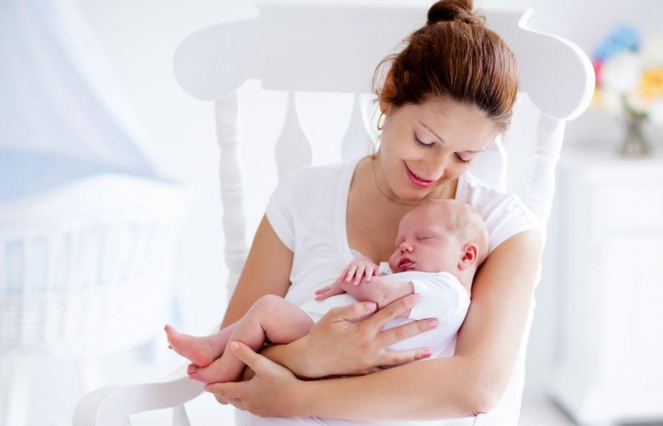 Frau hält schlafendes Baby