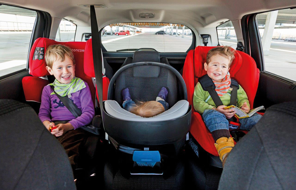 Drei Kinder sitzen in Autokindersitzen