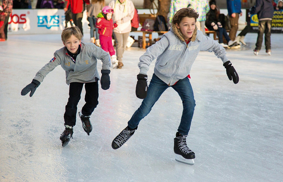 Zwei schlittschuh-fahrende Jungen auf einer Eisbahn