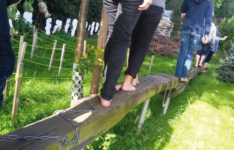 Mehrere Menschen laufen barfuß über einen Holzbalken