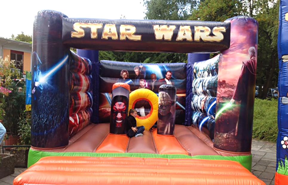 Kinder hüpfen in einer Star Wars Hüpfburg