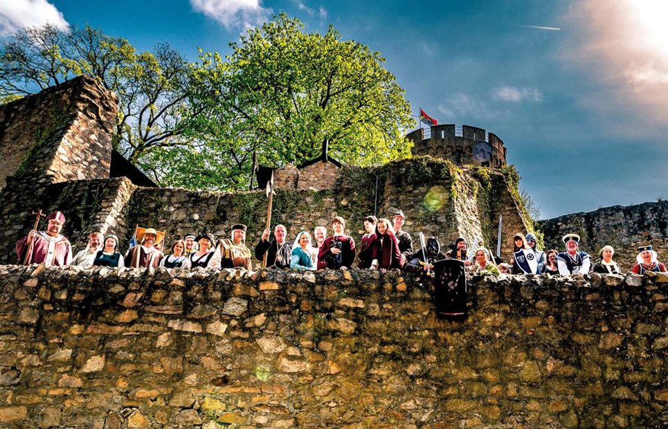 Mittelalterlich Gekleidete schauen von der Schlossmauer hinunter