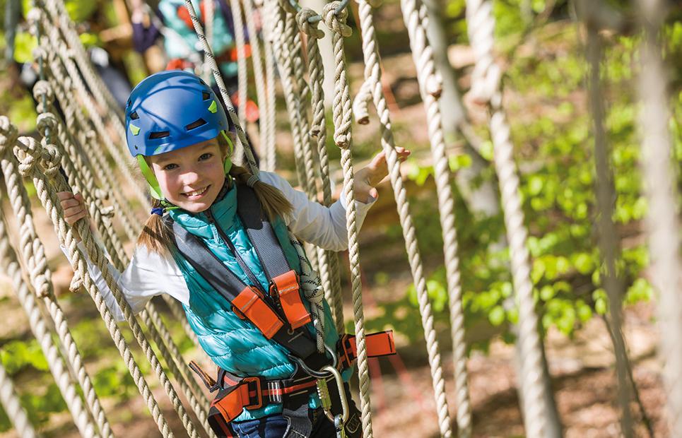 Ein Mädchen mit blauem Helm und Sicherheitsgeschirr klettert durch den Kletterwald
